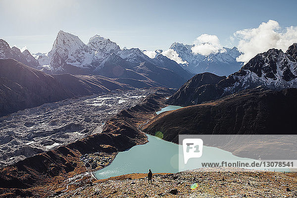 High angle view of silhouette hiker standing by lake amidst mountains against blue sky