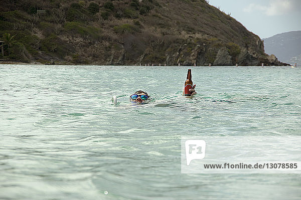 Man holding beer bottle while swimming in sea