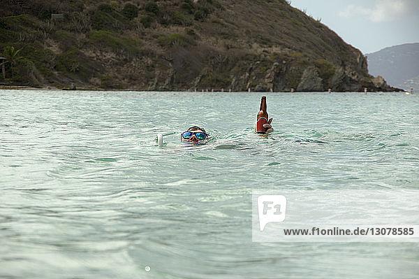 Mann hält Bierflasche beim Schwimmen im Meer