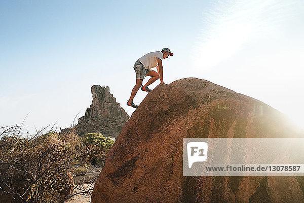 Tiefblick auf einen Mann  der am Fels gegen den klaren Himmel in der Wüste klettert