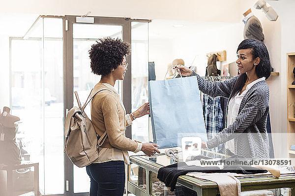 Saleswoman giving bag to customer at textile shop