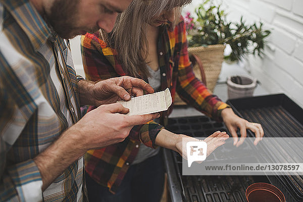 Man reading instruction while woman sprinkling seed on seedling tray
