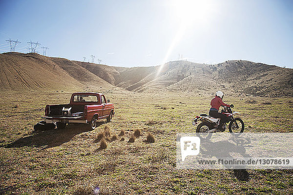 Rear view of female biker riding motorcycle on arid landscape during summer