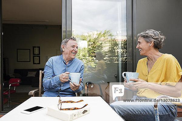 Glückliches älteres Ehepaar trinkt Kaffee auf der Veranda