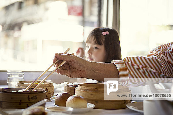 Cropped image of grandfather taking dumplings while sitting with granddaughter in restaurant