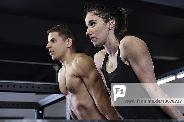 Low angle view of determined male and female athletes exercising in gym
