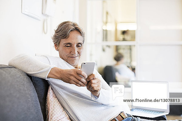 Mature woman using smart phone while sitting on sofa at home
