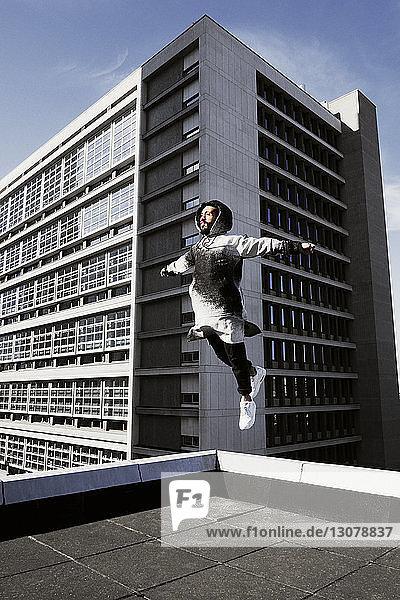 Mann springt auf Terrasse gegen Gebäude