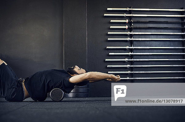 Side view of man exercising on barbell in gym
