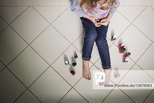 High angle view of girl with various nail polish bottles sitting on floor at home