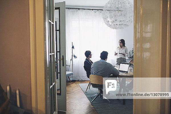 Geschäftsleute  die im Büro diskutieren  durch die Tür gesehen