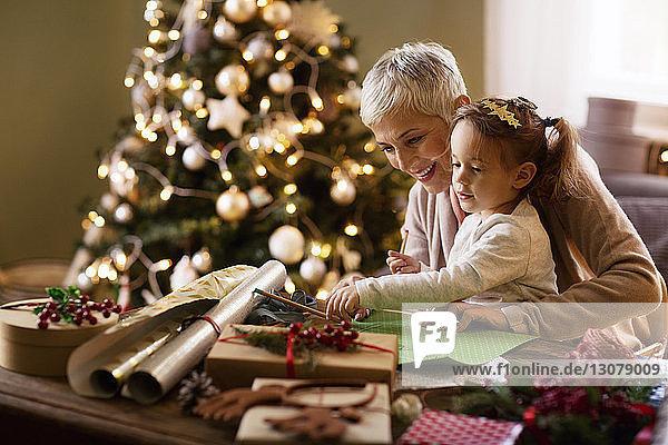 Großmutter hilft Enkelin beim Zeichnen zu Hause