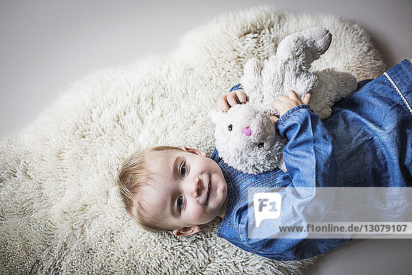Portrait of cute girl with stuffed toy lying on rug at home