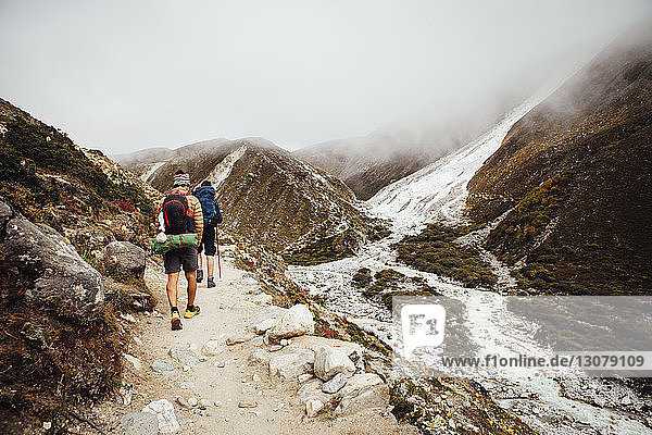 Rear view of friends with backpacks hiking at Sagarmatha National Park during foggy weather