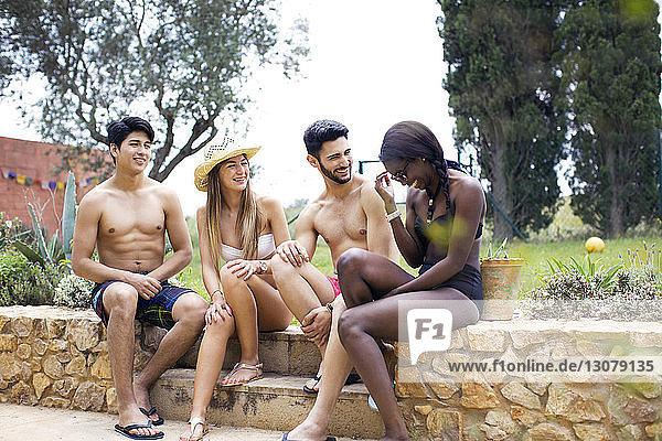 Glückliche Freunde in Badebekleidung sitzen auf der Stützmauer im Hof