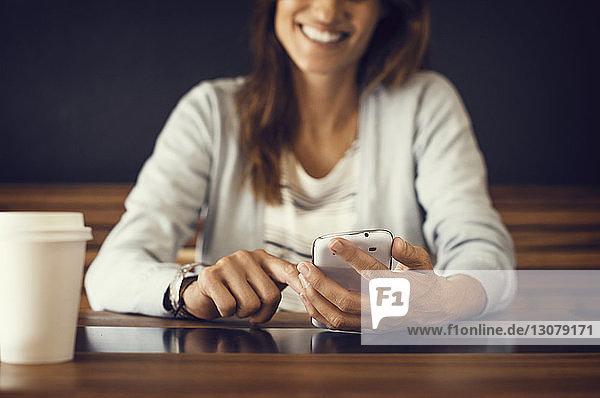Mitschnitt einer lächelnden Frau  die im Café ein Mobiltelefon benutzt