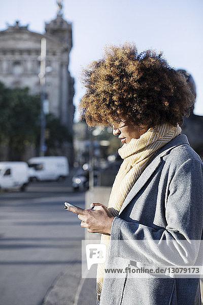Frau benutzt Mobiltelefon  während sie auf der Straße in der Stadt steht