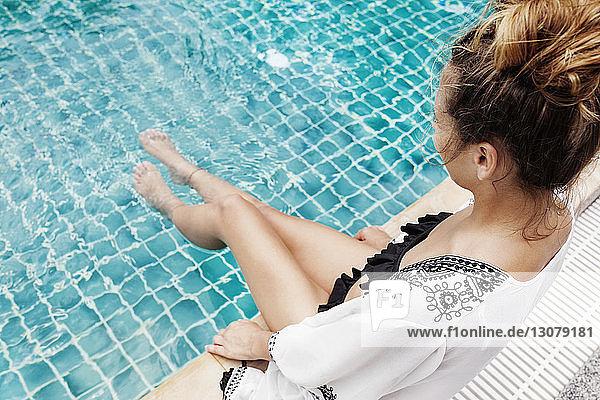 Hochwinkelansicht einer am Pool sitzenden Frau