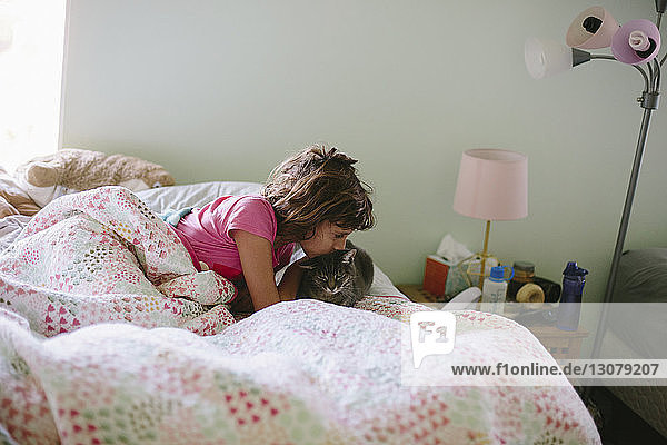 Girl kissing cat on bed at home