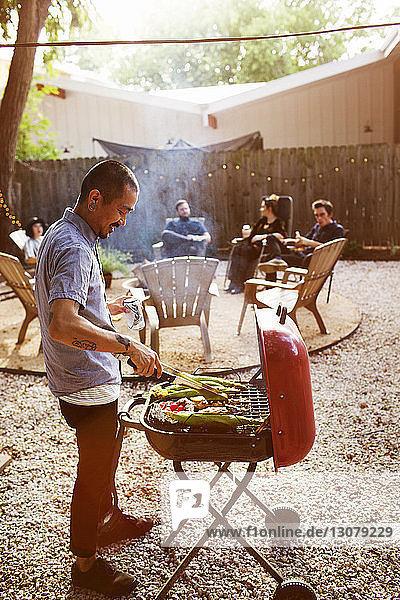 Mann grillt  während Freunde im Hof sitzen