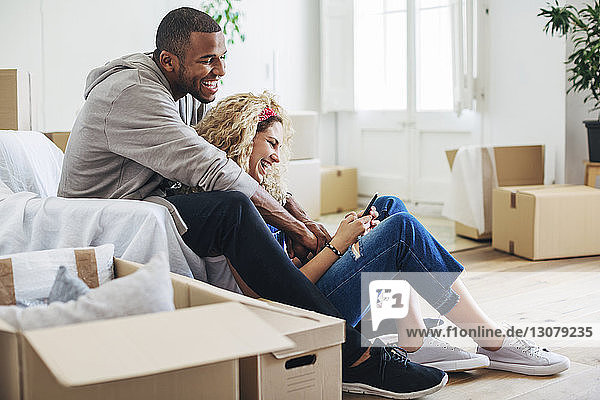 Happy couple using mobile phone while sitting at new house
