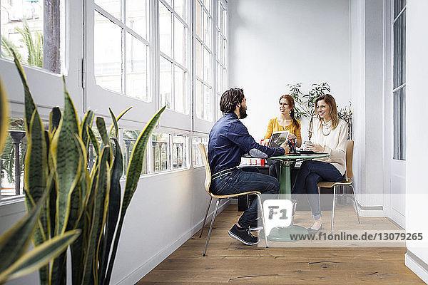 Fröhliche Geschäftsleute diskutieren bei Treffen im Kreativbüro