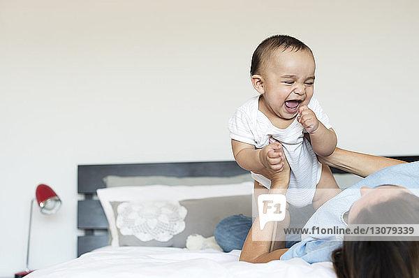Fröhlicher kleiner Junge spielt zu Hause mit der Mutter im Bett