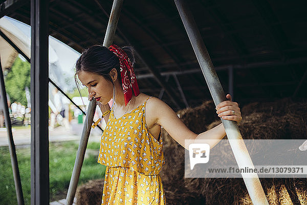 Zuversichtliche Frau schaut nach unten  während sie am Stall gegen Strohhalme steht