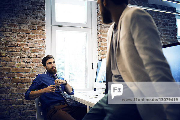 Male colleagues having discussion in office
