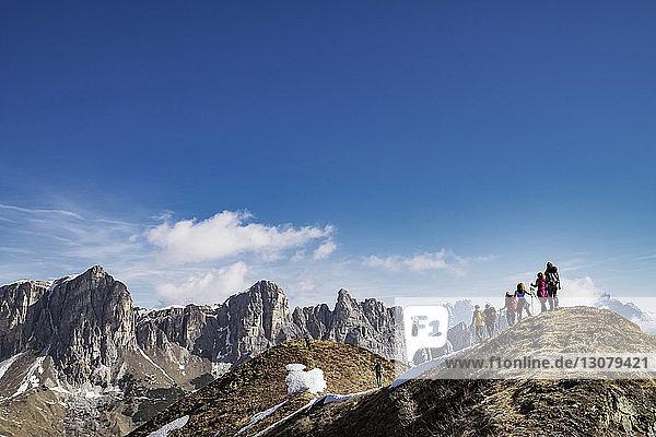 Rückansicht von Bergwanderern vor blauem Himmel