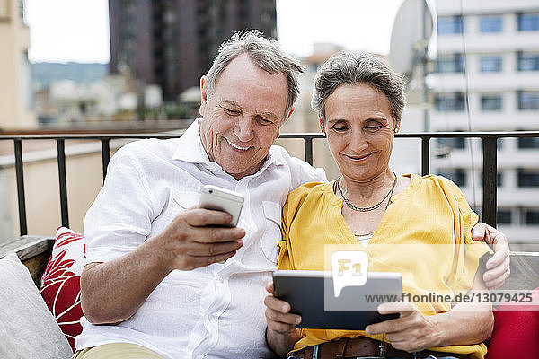 Happy senior couple using smart phone and tablet computer on terrace