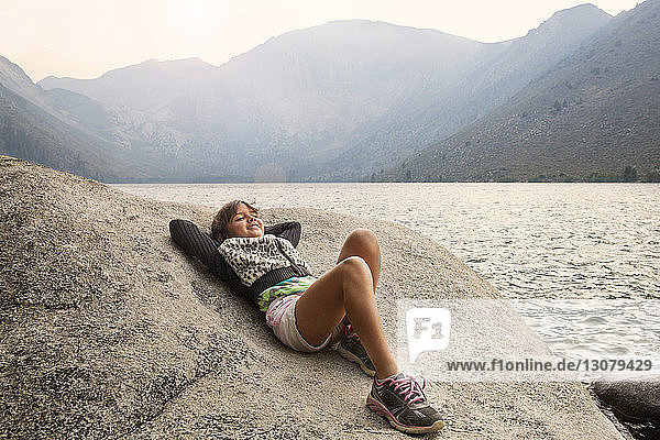 Happy girl relaxing on rock against Convict Lake and mountains
