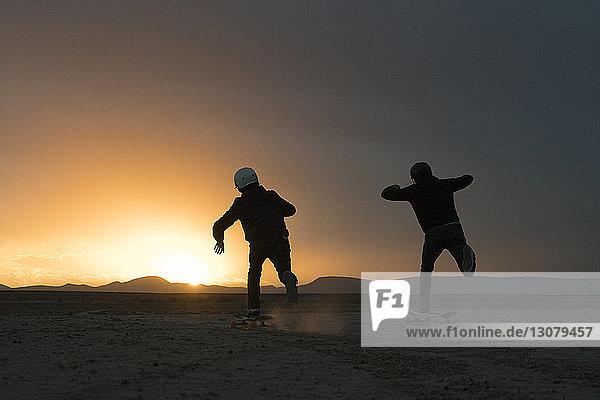 Rückansicht von Freunden  die bei Sonnenuntergang gegen den Himmel skateboarden