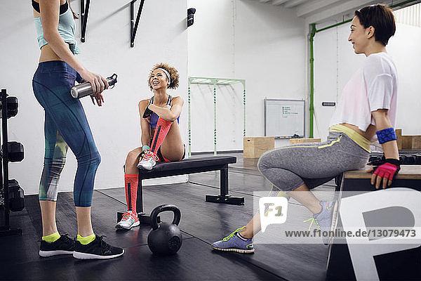 Happy female friends talking in gym