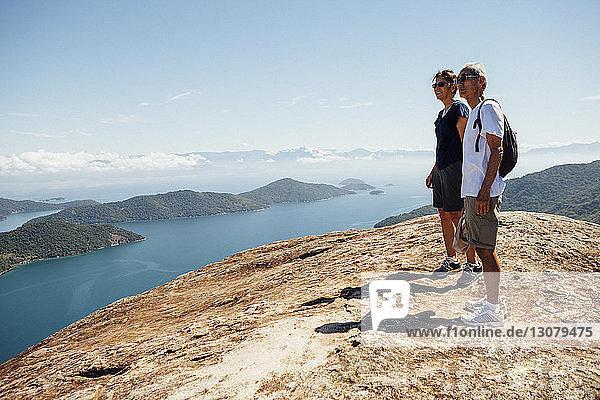 Freunde schauen auf die Aussicht  während sie bei Sonnenschein auf dem Berg gegen den Himmel stehen