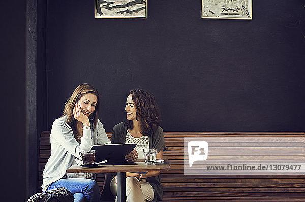 Glückliche Freundinnen mit Tablet-Computer im Café