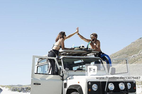 Freunde beim Hochspringen über das Autodach  während sie auf einem Geländewagen vor strahlend blauem Himmel stehen