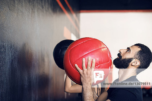 Side view of man throwing medicine ball at gym