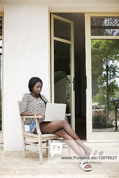 Young woman using laptop while sitting on chair at porch