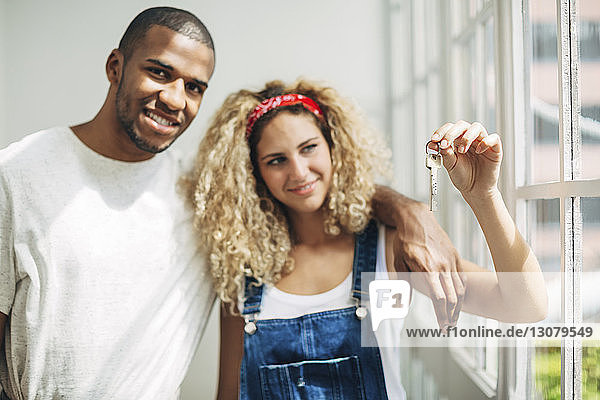 Portrait of man standing with wife looking at keys while standing by window in house