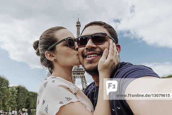 Portrait of girlfriend kissing boyfriend against Eiffel Tower in city