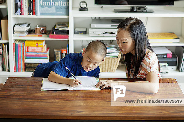 High angle view of mother assisting son in homework while sitting at home