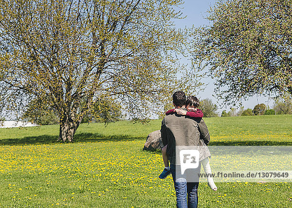 Rear view of father carrying son with broken leg on grassy field at park