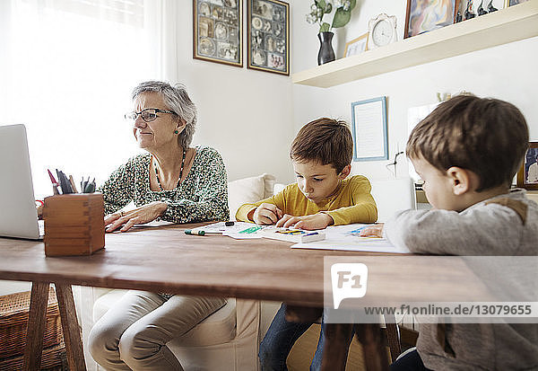 Boys making drawings while grandmother using laptop at home