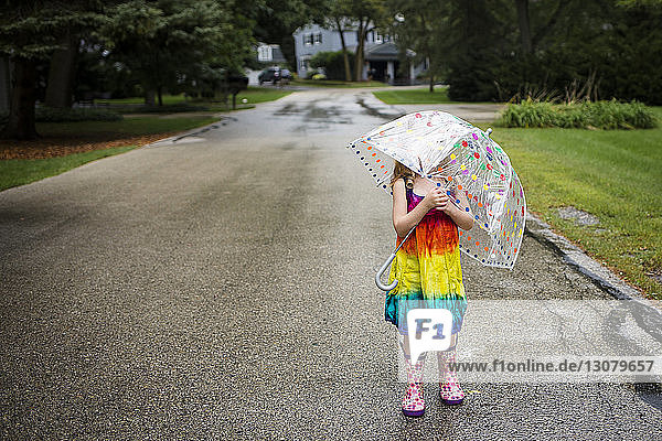 Girl carrying umbrella while standing on wet road