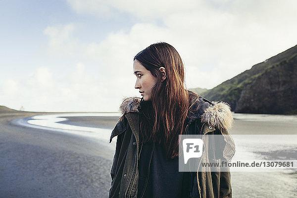 Schöne Frau steht am Bethells-Strand gegen den Himmel