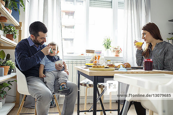 Woman looking at husband feeding son at table in kitchen
