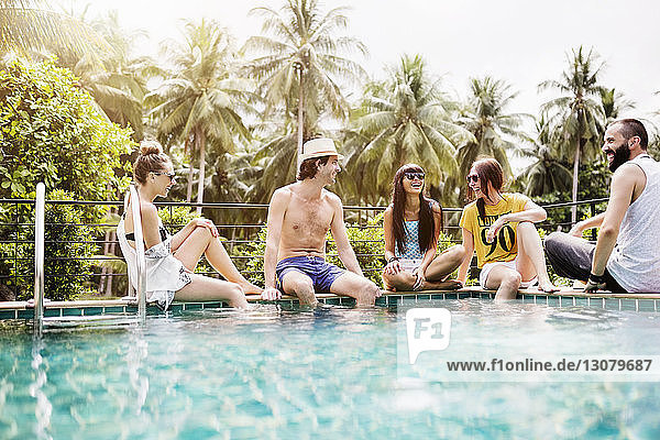 Fröhliche Freunde verbringen ihre Freizeit am Pool