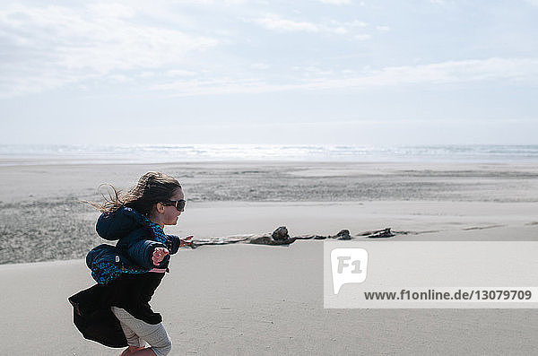 Side view of girl with arms outstretched running on beach against sky