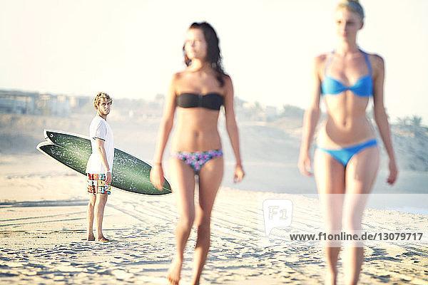Man looking at women in bikini walking on sand at beach